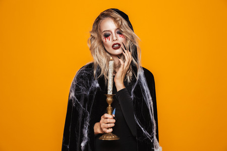 Young wizard woman 20s wearing black costume and halloween makeup holding candle isolated over yellow background