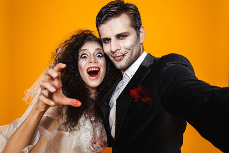 Photo of spooky zombie couple bridegroom and bride wearing wedding outfit and halloween makeup laughing while taking selfie isolated over yellow background
