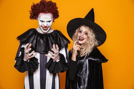 Imagen de mujer bruja y payaso hombre vestido con traje negro y maquillaje de halloween sonriendo a la cámara aislada sobre fondo amarillo