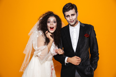 Photo of terrifying zombie couple bridegroom and bride wearing wedding outfit and halloween makeup looking at you isolated over yellow background