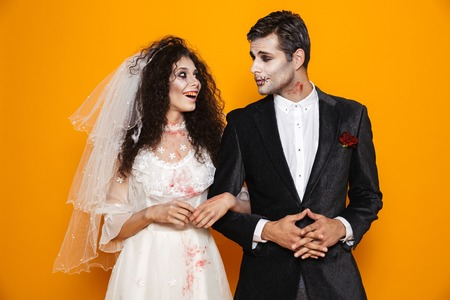 Cheerful dead bride and groom with halloween make-up looking at each other and smiling isolated over orange