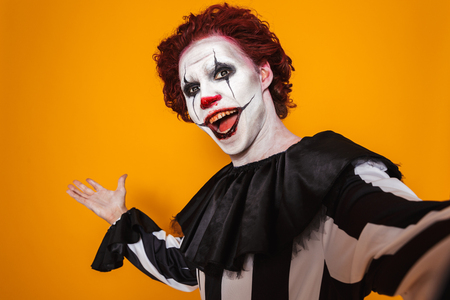 Angry man dressed in scary clown Halloween costume isolated over yellow background, taking a selfie Foto de archivo