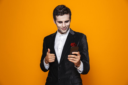 Photo of terrifying dead man on halloween wearing classical suit and creepy makeup holding mobile phone isolated over yellow background
