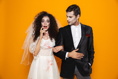 Photo of young zombie couple bridegroom and bride wearing wedding outfit and halloween makeup looking at camera isolated over yellow background Stock Photo