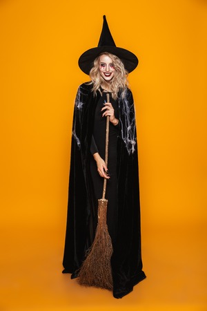 Full-length shot of cheerful woman witch in hat holding broom and smiling to camera isolated over orange