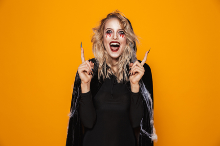 Happy scary witch in black clothes looking and pointing up at copy space isolated over orange