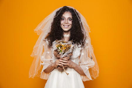 Cheerful dead bride in wedding dress and with halloween make-up holding flowers and smiling to camera isolated over orange Archivio Fotografico