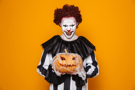 Mad man dressed in scary clown Halloween costume holding curved pumpkin isolated over yellow background Banco de Imagens