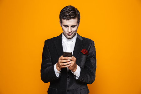 Photo of european dead man on halloween wearing classical suit and creepy makeup holding mobile phone isolated over yellow background