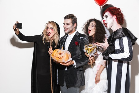 Group of excited friends dressed in scary costumes celebrating Halloween isolated over white background, holding balloons, curved pumpkin, taking a selfie