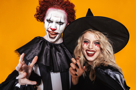 Image of witch woman and clown man wearing black costume and halloween makeup scaring at camera isolated over yellow background