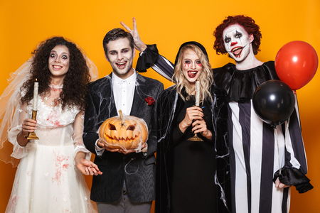 Group of cheerful dressed in scary costumes celebrating Halloween isolated over yellow background, holding balloons, curved pumpkin