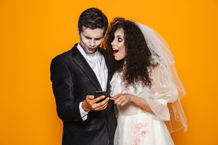 Photo of beautiful zombie couple bridegroom and bride wearing wedding outfit and halloween makeup using smartphone isolated over yellow background