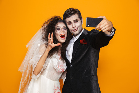Photo of joyful zombie couple bridegroom and bride wearing wedding outfit and halloween makeup laughing while taking selfie isolated over yellow background