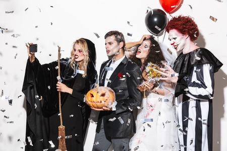 Group of excited friends dressed in scary costumes celebrating Halloween under confetti rain isolated over white background, holding balloons and curved pumpkin, taking a selfie 版權商用圖片