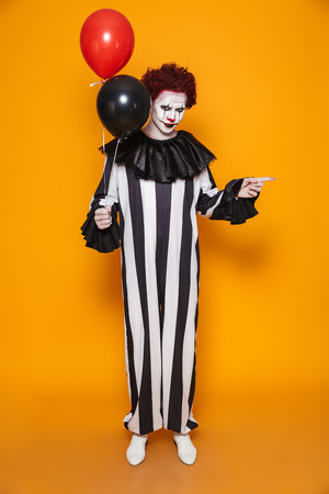 Young clown man 20s wearing black costume and halloween makeup grimacing and holding balloons isolated over yellow background