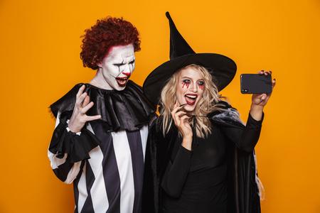 Photo of happy witch woman and joker man wearing black costume and halloween makeup taking selfie on smartphone isolated over yellow background
