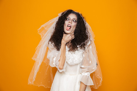 Image of dead bride zombie on halloween wearing wedding dress and scary makeup choking herself isolated over yellow background