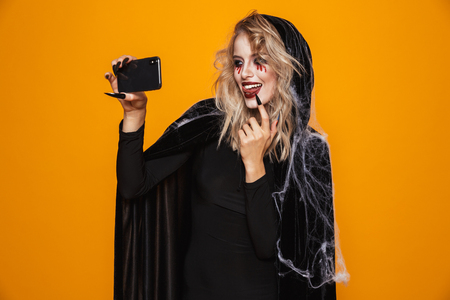 Pretty blonde lady witch with scary make-up making selfie on smartphone and smiling isolated over orange Zdjęcie Seryjne