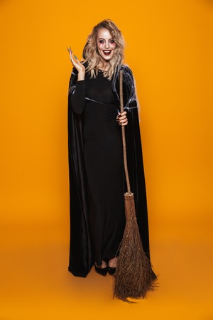 Full-length shot of cheerful woman witch holding broom and smiling to camera isolated over orange Stock Photo