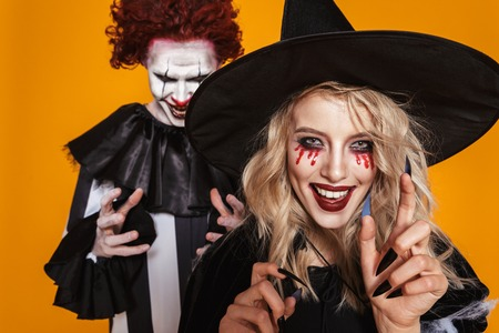 Scary wizard and clown in costumes and with halloween make-up looking and smiling to camera isolated over orange