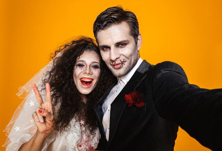 Photo of beautiful zombie couple bridegroom and bride wearing wedding outfit and halloween makeup laughing while taking selfie isolated over yellow background