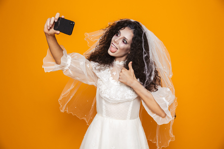 Cheerful bride zombie in wedding dress and veil making selfie on smartphone isolated over orange