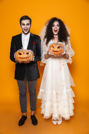 Full length photo of terrifying zombie couple bridegroom and bride wearing wedding outfit and halloween makeup holding carved pumpkin isolated over yellow background Stock Photo