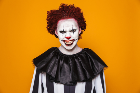 Angry clown man 20s wearing black costume and halloween makeup looking at camera isolated over yellow background Stock Photo - 112484798