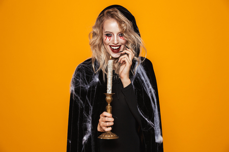 Tricky happy woman witch in black looking camera and holding candle isolated over orange