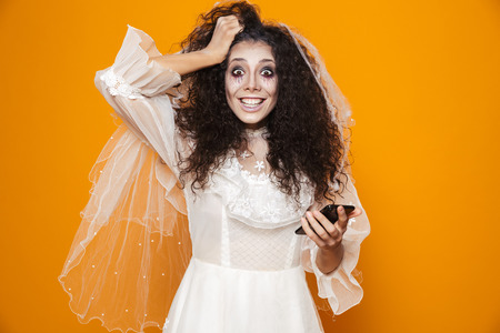 Image of happy zombie woman on halloween wearing wedding dress and holiday makeup using cell phone isolated over yellow background Stock Photo