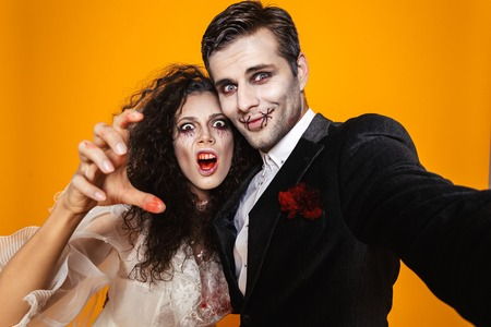Funny pretty zombie bride and groom in halloween costumes making selfie at camera and smiling isolated over orange
