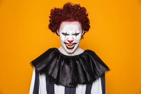 Tricky scary man clown in costume looking camera with anger and smiling isolated over orange