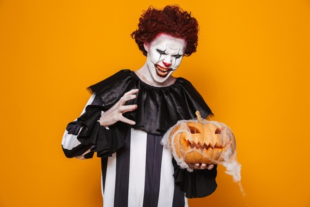 Angry man dressed in scary clown Halloween costume holding curved pumpkin isolated over yellow background