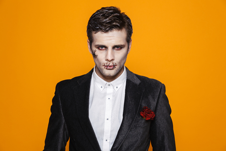 Serious zombie groom in official suit and with halloween make-up looking camera isolated over orange