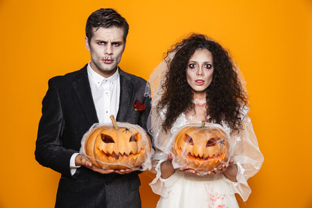 Photo of beautiful zombie couple bridegroom and bride wearing wedding outfit and halloween makeup holding carved pumpkin isolated over yellow background