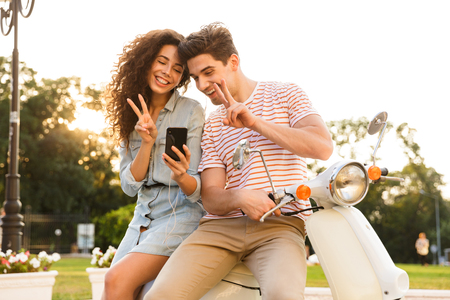 Portrait of beautiful couple man and woman wearing earphones smiling at smartphone while sitting on scooter together on city street