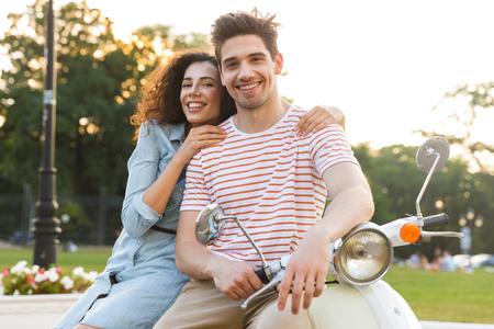 Porträt eines entzückenden Paares, Mann und Frau, die zusammen lächeln und sich umarmen, während sie auf dem Motorrad im Stadtpark sitzen?