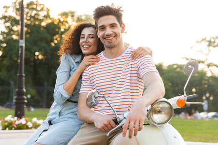 Portrait of adorable couple man and woman smiling and hugging together while sitting on motorbike in city park 스톡 콘텐츠 - 111857804