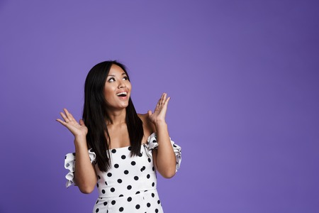 Portrait of a cheerful asian woman in dress standing isolated over violet background, celebrating, looking away Stockfoto