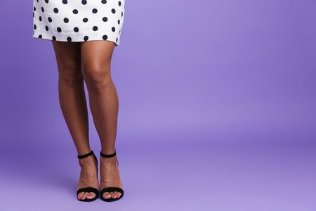 Close up of a woman in dress with long legs and high heels isolated over violet background