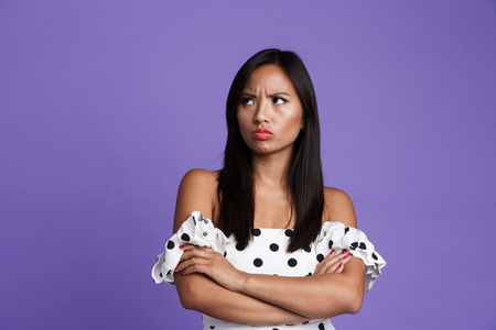 Portrait of an upset asian woman in dress standing isolated over violet background , presenting copy space Banco de Imagens - 111859151