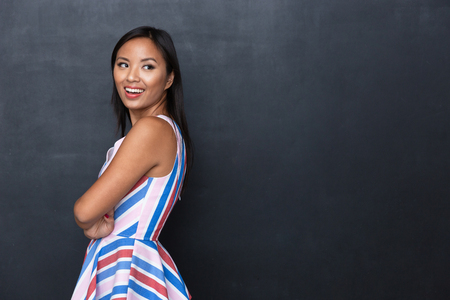 Portrait of a cheerful casual asian woman standing isolated over gray background, looking away Stock fotó