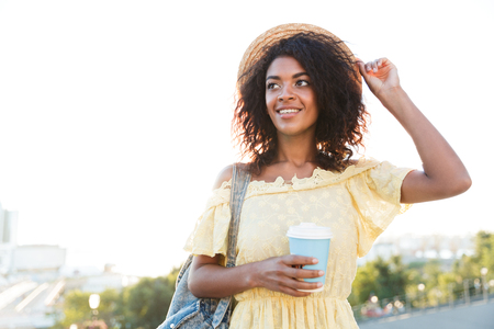 Cheerful young african woman in summer dress walking at the city, holding cup of coffee Stock Photo