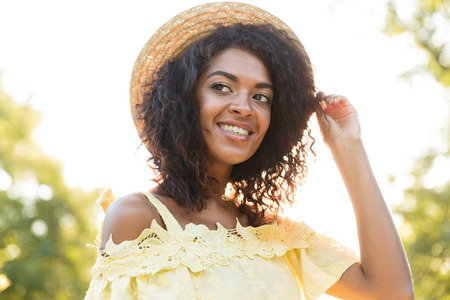 Photo of gorgeous african american woman 20s wearing straw hat and dress smiling while sitting on bench in park Stock Photo