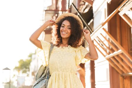 Portrait of gorgeous african american woman 20s wearing straw hat and dress walking outdoor during sunny day