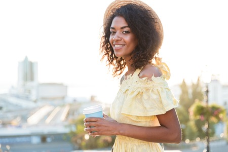 Lovely young african woman in summer dress walking at the city, holding cup of coffee