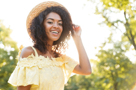 Photo of pretty african american woman 20s wearing straw hat and dress smiling while sitting on bench in park