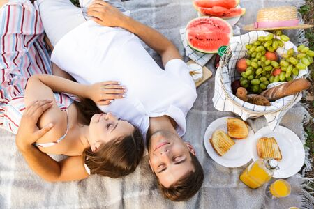 Top view of a lovely young couple laying on a blanket, having picnic