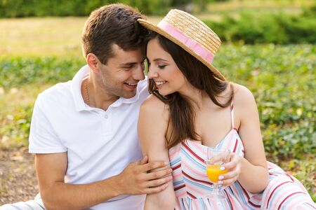 Happy young couple spending good time together, having picnic at the park